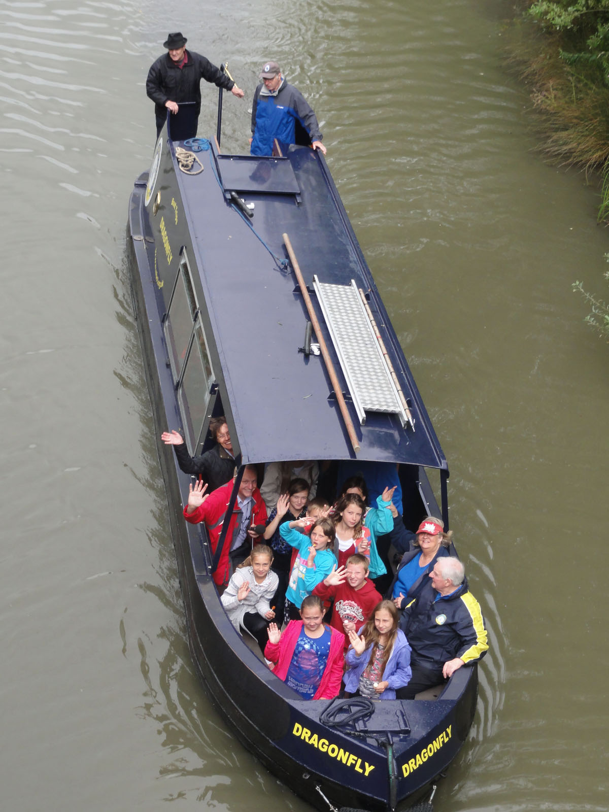View looking down on trip boat Dragonfly from bridge, passengers waving